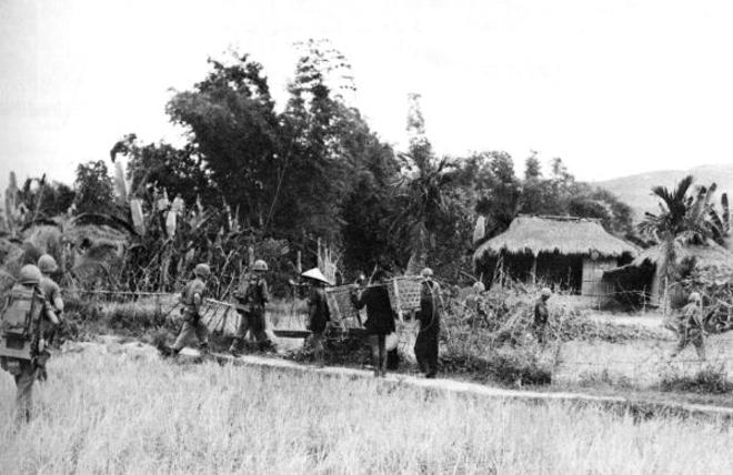 In one of the first extensions of Marine positions into a populated area in May, Marines from the 2d Battalion, 3d Marines move into the hamlet of Le My. Three villagers watch the troops enter the village gate.