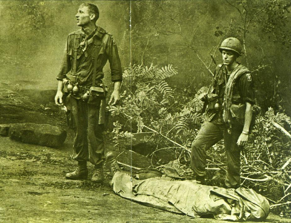 "Ruediger Richter of the 4th Battalion, 503rd Infantry, 173rd Airborne Brigade, lifts his battle weary eyes to the heavens, as if to ask ""Why?"" Sergeant Daniel E. Spencer stares down at their fallen comrade. The day's battle ended, they silently await the helicopter which will evacuate their comrade from the jungle covered hills. Photo by Paul Epley (August 14th, 1966)"